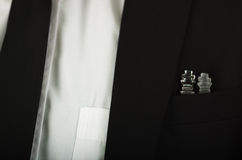 Closeup black suit jacket chest pocket with glass chess pieces sitting inside, white shirt and tie visible Stock Image
