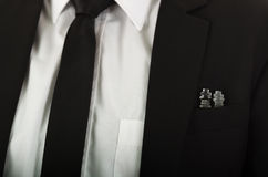 Closeup black suit jacket chest pocket with glass chess pieces sitting inside, white shirt and tie visible Royalty Free Stock Photography