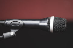 Closeup black vocal microphone mounted on mic stand, blurry red dark bcakground Stock Photos