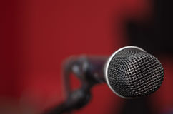 Closeup black vocal microphone mounted on mic stand, blurry red dark bcakground Stock Image