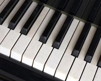 Black and white keys on old ivory keyboard of grand piano. Closeup of black and white keys on old ivory keyboard of antique bechstein grand piano Stock Photos