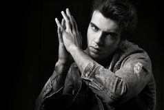 Closeup of black and white masculine portrait on a black background. Young handsome man posing and looking at camera. Fashion photograph professional models stock images