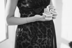 Closeup black and white photo of pregnant woman. Black and white photo of pregnant woman showing baby shoes Royalty Free Stock Photos