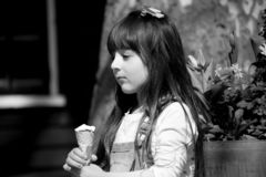 Closeup of black and white photo of 6 years old Little child girl kid portrait walking along city street and eating ice cream alon stock photo