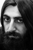 Closeup black-and-white portrait of a bearded man with long hair. Royalty Free Stock Photo