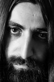 Closeup black-and-white portrait of a bearded man with long hair. Royalty Free Stock Image