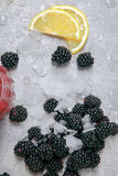 Closeup of blackberries with ice and slices of sappy lemon on a moist table with drops of water on a grey background. Closeup of fresh blackberries mixed with Stock Photography