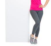 Closeup on blank billboard and fitness woman legs Stock Image