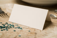 Closeup of Blank Place Card by a Plate, Fork, and Green Sequins Stock Photo