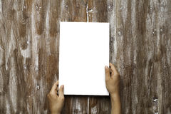 Closeup Blank White Paper Sheet Mockup Holding Male Hands Natural Wood Table Background. Empty Canvas Painted Brown Desk.  Royalty Free Stock Image