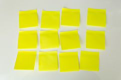 Closeup of 12 blank yellow sticky notes on white board Stock Image