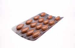 Closeup of blister with orange pills. Blister with orange pills isolated on white Royalty Free Stock Images