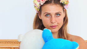 Closeup blond girl in garland hugs soft toy in armchair stock footage