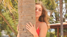 Closeup blond girl in red hides behind palm smooths hair stock footage