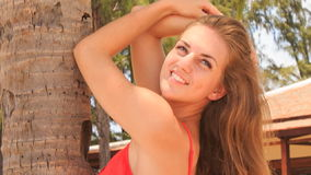 Closeup blond girl in red leans on palm trunk smiles stock video