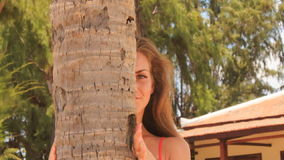 Closeup blond girl in red looks out of palm trunk and speaks stock footage