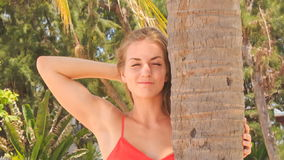Closeup blond girl in red touches palm smooths hair stock footage