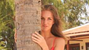 Closeup blond girl in red tries hide behind palm trunk smiles stock video