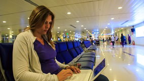 Closeup Blond Girl Sits on Chair Works on Laptop in Terminal stock footage
