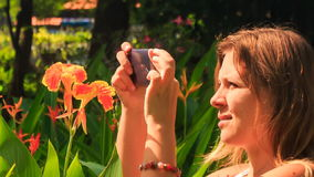 Closeup Blond Girl Takes Photo of Tropical Flower in Park stock video footage