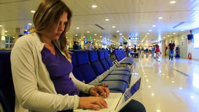 Closeup Blond Girl Tapes Text on Laptop in Airport Terminal stock video footage