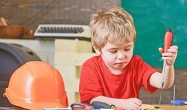 Closeup blond kid in workshop. Boy binding screws to wooden board. Concentrated child learning new skills.  stock photo