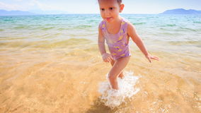 Closeup Blond Little Girl Runs out of Sea to Sand Beach. Closeup blond little girl with pigtail runs out of transparent shallow azure sea to sand beach against stock video footage