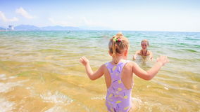 Closeup Blond Little Girl Runs out of Sea to Sand Beach. Closeup blond little girl with pigtail runs out of transparent shallow azure sea to sand beach against stock video