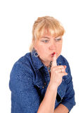 Closeup of blond woman with finger over mouth. Stock Image