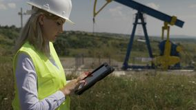 Closeup of blonde attractive engineer woman supervising oil pumping near a unit using digital tablet -. Closeup of blonde attractive engineer woman supervising stock video footage