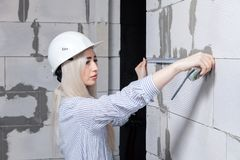 Closeup blonde girl designer foreman in white construction helmet measures the grey wall of sibit by tape measure in house under. Closeup blonde girl designer royalty free stock images
