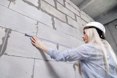 Closeup blonde girl designer foreman in white construction helmet measures the grey wall of sibit by tape measure in house under. Closeup blonde girl designer royalty free stock image