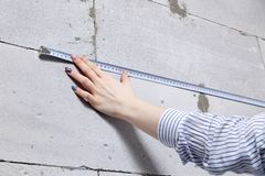 Closeup blonde girl designer foreman in white construction helmet measures the grey wall of sibit by tape measure in house under. Closeup blonde girl designer royalty free stock photo