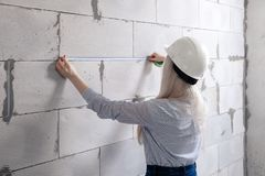 Closeup blonde girl designer foreman in white construction helmet measures the grey wall of sibit by tape measure in house under royalty free stock images