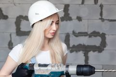 Closeup blonde girl foreman in white construction helmet holding professional perforator, drill in house under construction. Concept worker, female labor, work stock images