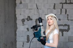 Closeup blonde girl foreman in white construction helmet holding professional perforator, drill in house under construction. Concept worker, female labor, work royalty free stock image