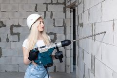 Closeup blonde girl foreman in white construction helmet holding professional perforator, drill in house under construction. Concept worker, female labor, work stock photo