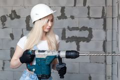 Closeup blonde girl foreman in white construction helmet holding professional perforator, drill in house under construction. Concept worker, female labor, work stock image