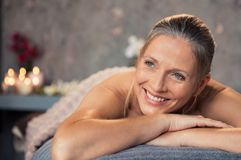Mature woman smiling at spa. Closeup of a blonde woman lying on a lounger in a wellness center for massage therapy. Portrait of a beautiful mature woman lying stock photos