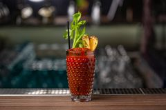 Closeup of a bloody mary cocktail garnished with a celery sick isolated on a busy bar top stock images
