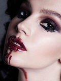 Closeup of bloody red lips young girl. Dark fashion beautiful br. Unette woman. Glamour sensual posing Stock Image