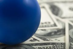 Closeup of blue ball on stack of cash Royalty Free Stock Photos