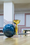Closeup of blue bowling ball near golden trophy Royalty Free Stock Photo