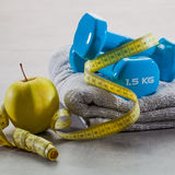 Closeup of blue dumbbells, apple, grey towel and measuring tape Stock Image
