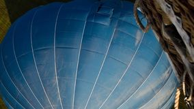Closeup of a blue hot air balloon with wicker basket stock images