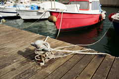 Closeup of a boat tied with a rope on a mooring. A closeup of a boat tied with a rope on a mooring Royalty Free Stock Image