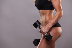 Closeup body of fitness woman with dumbbells . Sporty girl showing her well trained body . isolated on grey background. With copyspace Stock Image
