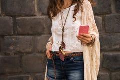 Closeup on boho young woman near stone wall writing sms Stock Image
