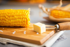 Closeup on boiled corn and butter on cutting board Royalty Free Stock Image