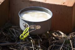 A closeup of a boiling pot on a gas primus cooking dinner for hikers. Royalty Free Stock Images